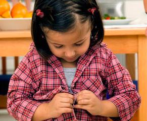 niño abotonándose la camisa
